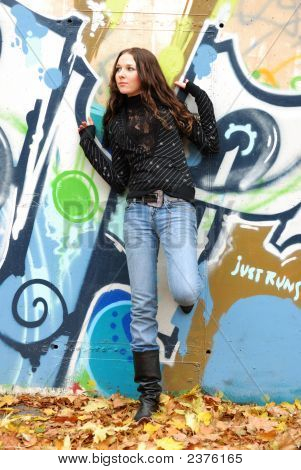 Young Model With Dark Hairs. Graffiti Wall. Fall. Autumn
