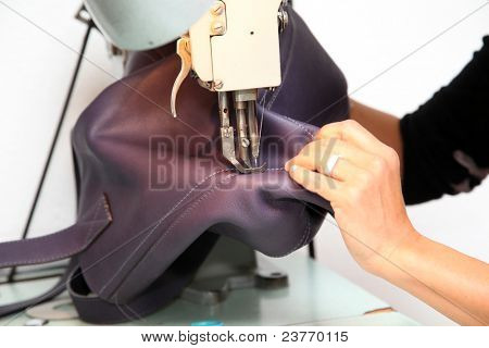Closeup on woman sewing leather handbag