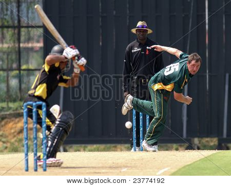 PUCHONG, MALAYSIA - SEPT 24: GM Smit, Guernsey bowls Rakesh Madhavan (5), Malaysia at the Pepsi ICC World Cricket League Div 6 finals at the Kinrara Oval on September 24, 2011 in Puchong, Malaysia.