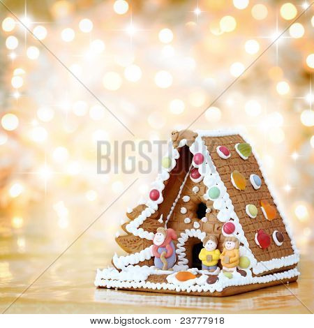 Christmas gingerbread house decoration on background of defocused golden lights. Hand decorated. Shallow DOF.