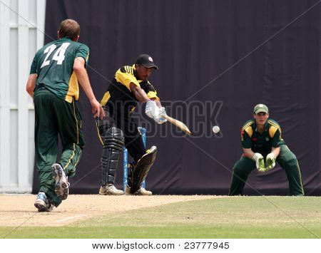PUCHONG, MALAYSIA - SEPT 24: Malaysia's Madhavan bats a Guernsey's (24) Adam Martel's bowl at the Pepsi ICC World Cricket League Div 6 finals at the Kinrara Oval on Sept 24, 2011 in Puchong, Malaysia.