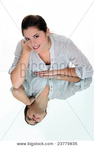 Smiling woman leaning on a mirrored surface
