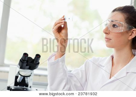 Beautiful science student looking at a microscope slide in a laboratory