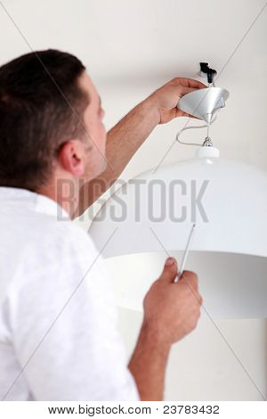 handyman fixate a lamp on the ceiling