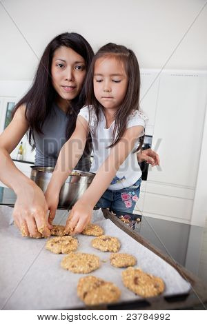 Portrait of mother and child in kitchen making cookies