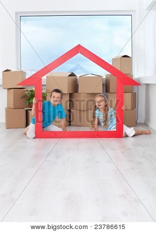 Kids in their new home holding large house shaped frame - moving concept with copy space
