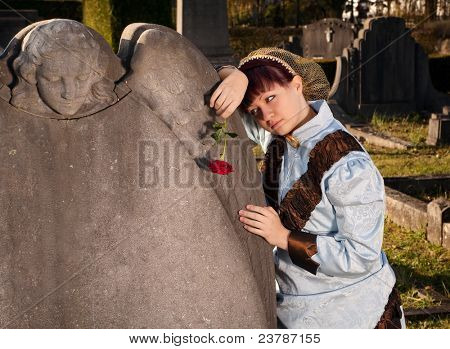 Mourning victorian lady holding a red rose in a graveyard