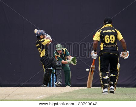 PUCHONG, MALAYSIA - SEPT 24: Malaysia's batsman Mohd Shafiq bats as Hammad (69) watches in this Pepsi ICC WCL Div 6 finals vs Guernsey at the Kinrara Oval on September 24, 2011 in Puchong, Malaysia.