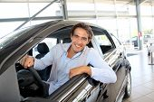 Smiling man sitting at the steering-wheel of brand new car poster