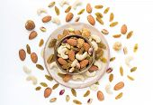 Dried fruits and variety of nuts in a bowl on the white table background, such as figs, almonds, raisins, cashews, and pistachio. with copy space for your text.