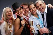 foto of christmas song  - Photo of businesspeople with flutes of sparkling champagne singing Christmas songs - JPG
