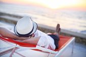 Young Man Relaxing On The Beach Back View. Summer Vacation. Relax Concept poster