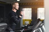 Young Handsome Man With Fitness Tracker In Sport Club. Cardio Workout, Running On Treadmill. Healthy poster