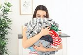 Woman holding heap of dirty clothes indoors. Laundry day poster