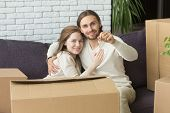 Portrait Of Happy Couple Holding Keys Embracing Sitting On Couch With Boxes In New Home, Smiling Ren poster
