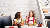 School Time Of Girls. Little Girls Eat Apple At Lunch Break. Happy School Kids At Lesson In Septembe poster