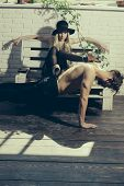 Muscular Man Training Sport At Pretty Young Girl. Retro Woman Put Legs On Back Of Muscular Man. Coup poster