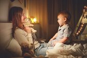 Mother Puts The Baby Son To Sleep In Evening In Bed In Dark poster