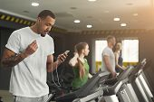 Young African-american Man With Smartphone Running On Treadmill In Gym. Fitness Guy Jogging In Fitne poster