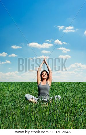 beautiful young woman meditating at the meadow at sunny day