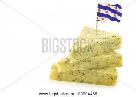 stacked pieces of traditional frisian cheese with herbs and a frisian flag toothpick on a white background