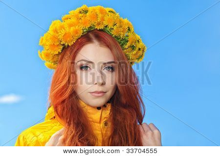 Beautiful young woman in a circlet of flowers over blue sky.