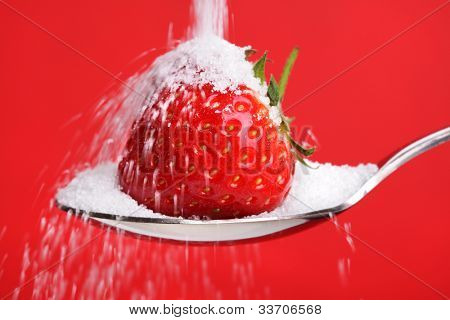 Pouring sugar over a strawberry on a spoon