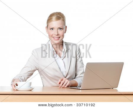 Young businesswoman sitting at a desk with a cup of tea, isolated