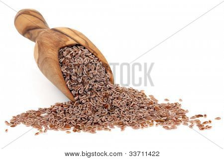 Pink psyllium seed in an olive wood scoop over white background.