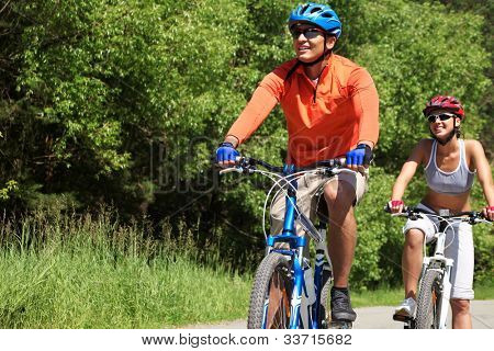 A young couple racing on bicycles in natural environment