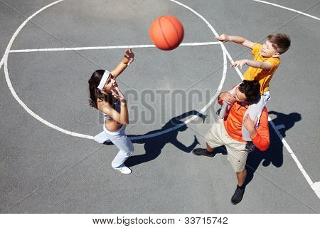 Image of sporty couple and their son playing with ball