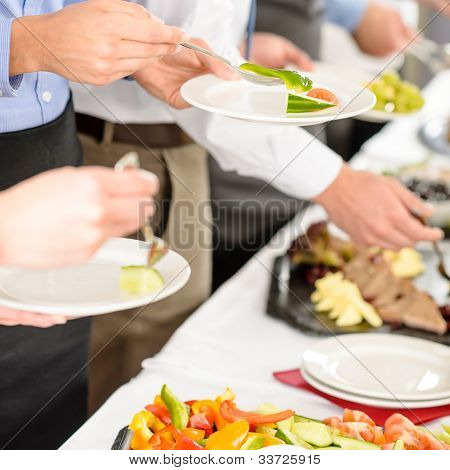 Business catering people take buffet food during company event