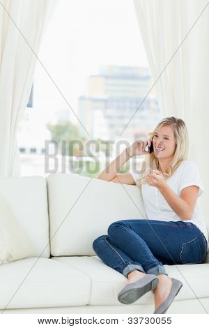 A smiling woman with her hand slightly raised as she sits on her couch making a call