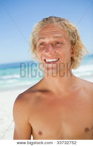 Surprised young blonde man looking towards the side while standing on the beach