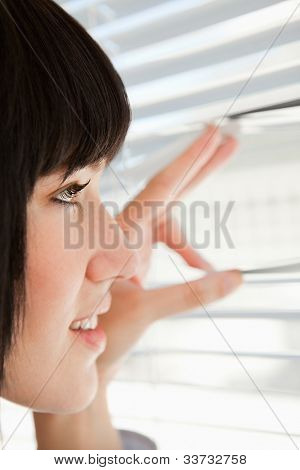 A close up shot of a woman looking through her window blinds