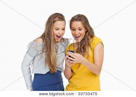 Two voiceless young women looking a smartphone against white background