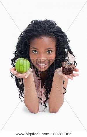 A smiling young woman is holding an apple and a bun on the palms of her arms against a white background