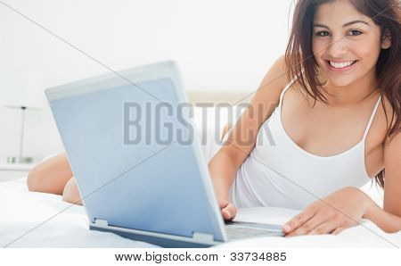 A woman lying on her bed as she interacts with her laptop while looking straight ahead and smiling.