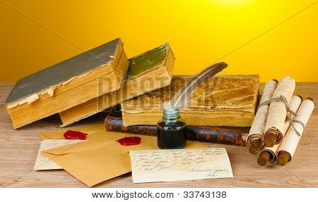 old books, scrolls, feather pen and inkwell on wooden table on yellow background