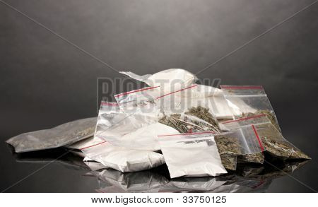 Cocaine and marihuana in packages on grey background