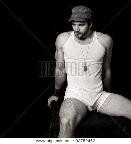 Sexy tough looking man in underwear and tank top and cap against black background