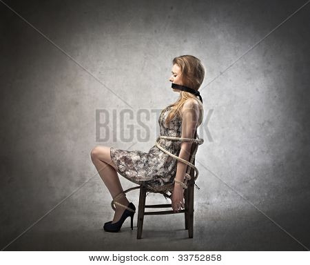 Young woman tied to a chair