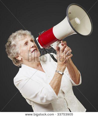 portrait of a senior woman holding a megaphone over a black background