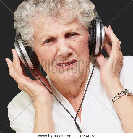portrait of a senior woman listening to music over a black background