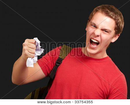 young angry student man roughing a sheet over a black background