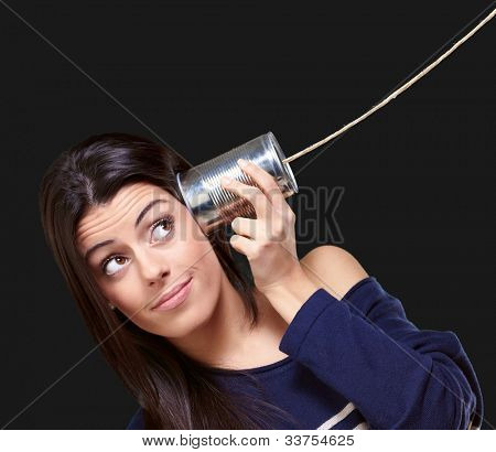portrait of a young woman hearing through a tin can over a black background