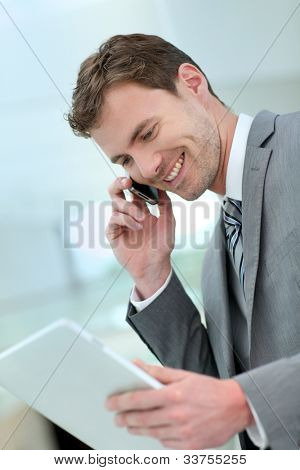 Smiling businessman having a phonecall in building hallway