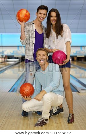 Two young men and beautiful girl hold balls in bowling club; focus on sitting man; shallow depth of field; full body