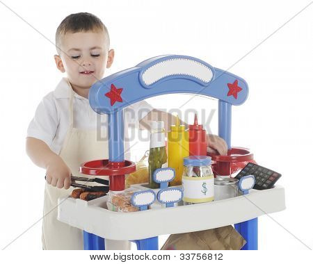 A young preschooler happily grilling hot dogs on his vending stand.  The stand's signs are left blank for your text.  On a white background.