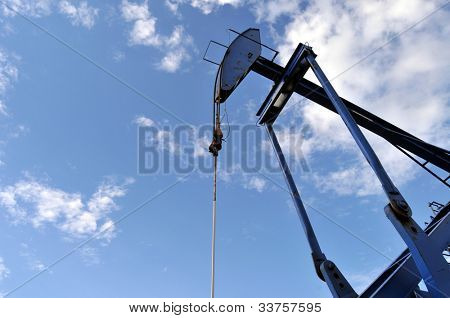 Low-angle closeup of a blue pump jack against the sky at an oil well
